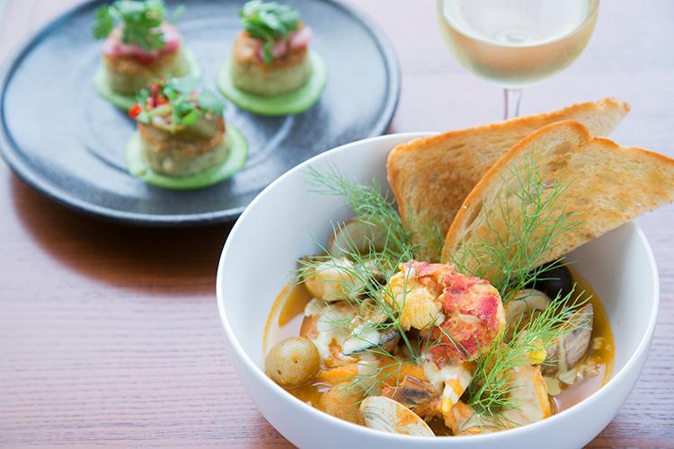 ディナーの新しい2品。地元魚介類を使ったシーフードシチュー(手前)$38と、魚菜主義の人向けに改良したクラブケーキ$24。