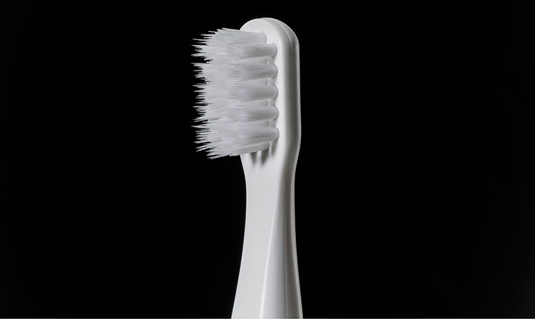 ブラシはデリケートな歯周ポケットに必要以上に入り込まないように、先端に3mmの段差を設けている。背面には舌ブラシを搭載。外出先で舌の汚れが気になるときに、しっかり除去できる。